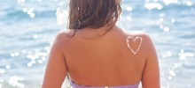 Woman with sunscreen tan lotion on her tanned back